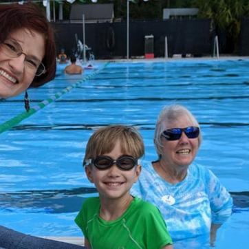 Mother and son in pool with swim instructor