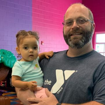 foster dad wearing YMCA shirt holding young daughter
