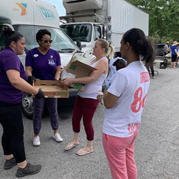 Tampa YMCA Veggie Van staff dispersing packages of produce