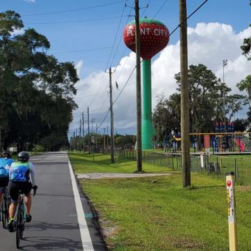 two bicyclists on road by Plant City water tower
