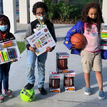 three kids wearing face coverings outdoors showing their new writing utensil kits and sports gear